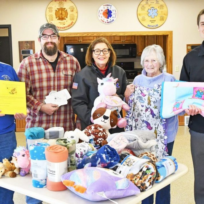 Pierce Rescue personnel accept a donation from St. John's Lutheran Church LWML JOY Circle. Pictured above, and accepting the gifts, are Pierce Rescue members, left to right: Karl Schultz, Josh Mattson, and Rhonda Rowley. Next to Rowley is JOY Circle President Janet Riedel, and St. John's Lutheran Church Rev. Jacob Tuma representing the church members that contributed to the donation.