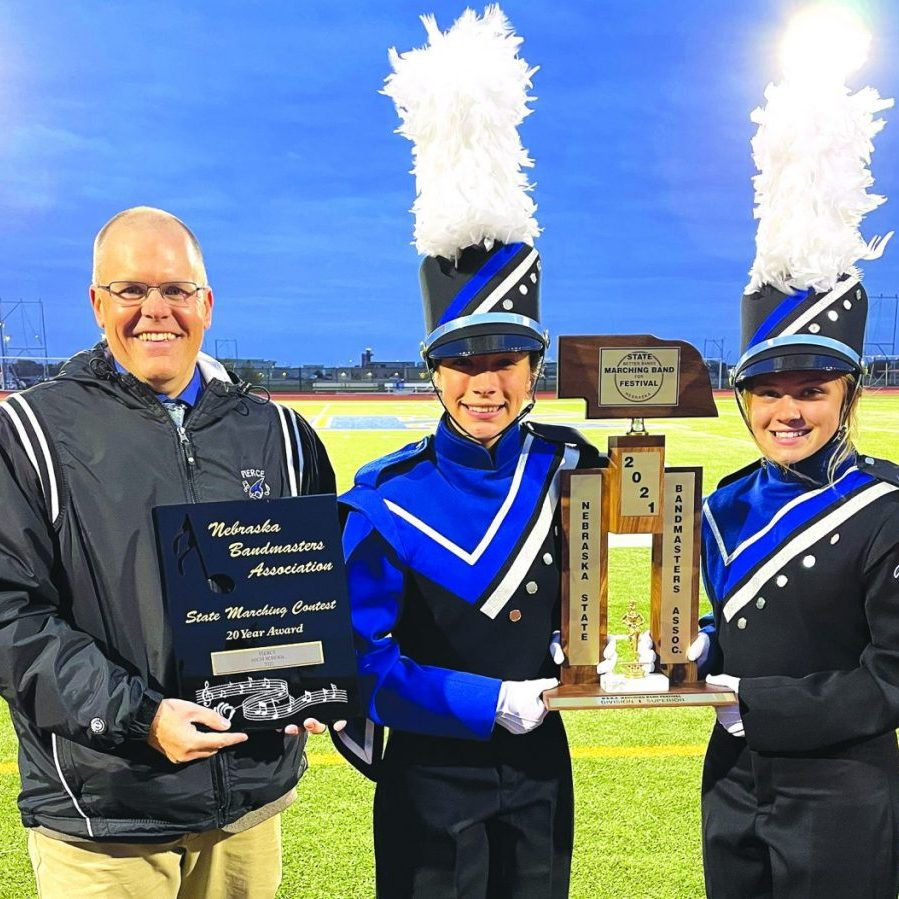 Band Director Mr. Mike Sindt smiles proudly with Drum Majors Alexus Sindelar and Callie Arnold after the Nebraska State Bandmasters Association State Marching Band Competition Saturday, October 23.